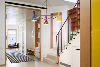 """Bold colors make the space feel """"exciting and intentionally present"""" with the staircase and active cabinetry establishing a stylish counterbalance opposite the kitchen."""