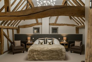 A staircase leads up to three bedrooms with ensuite baths and exposed timber wall and ceiling beams.