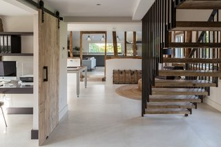 The steel balustrade of the staircase complements the industrial-style Crittall windows used throughout the house.