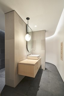 The guest bathroom features a Gala pendant designed by Rich Brilliant Willing.