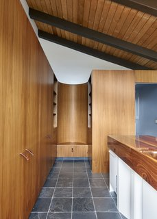 The architects made the sink the center of the bathroom and then designed everything else to orbit around it. The result is a bathroom that feels remarkably airy for its size. A local craftsman made the custom stamped saddle leather pulls.