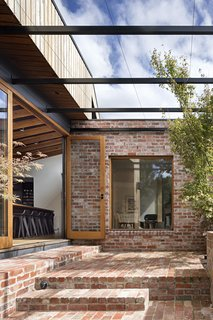 A steel pergola creates an outdoor living space; in the summer, grape vines climb up to create a lush canopy.