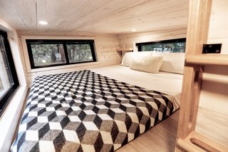 When it comes to bedroom lighting ideas, a low ceiling often works best with out-of-the-way recessed lighting, seen here in this tiny trailer. The recessed lights provide just the right amount of task lighting, while the surrounding windows lend natural light.