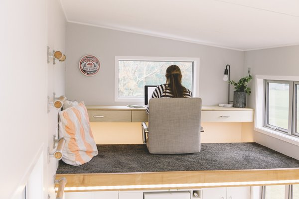A cozy, carpeted, lofted office is one of the highlights of this tiny home.