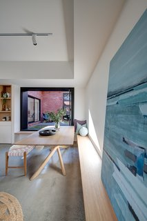 A built-in bench wraps around a corner as seats for the dining table. The artwork is by watercolorist Stefan Gevers.