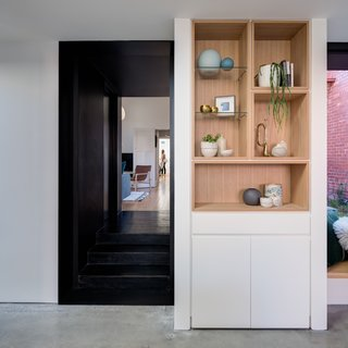Oak timber recessed 'boxes' are used as bookshelves, wine storage, and display cabinets.