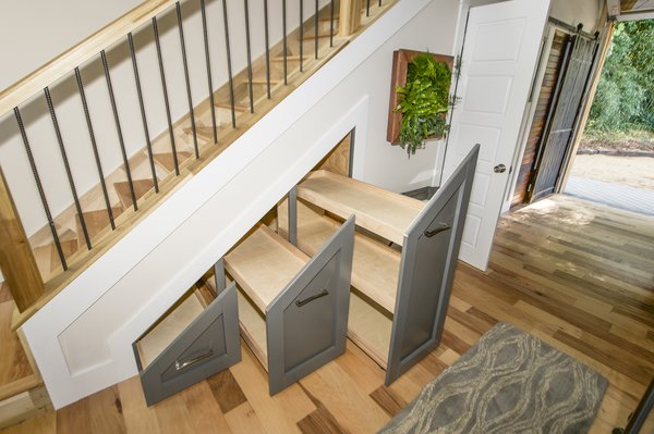 The cabinets under the stairs are ideal for shoe racks.