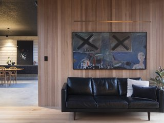 A painting by artist Peter Stephenson hangs in the lounge room, the colors offset by the varying hues of ash wood.