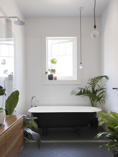 Potted plants add a sense of calm to the minimalist bathroom.