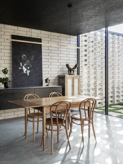 A Nathan Grey painting carries the dark motif of the kitchen into the dining space.