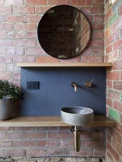 Hobart-based ceramic artist Lindsey Wherrett and Archier collabrated to create the round bathroom sink, whose tones take inspiration from the Mount Wellington undergrowth.