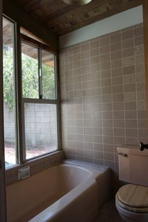 """""""The master was the biggest challenge. It was a divided space with a vanity area that was open to the bedroom. A small separate (carpeted!) room held a shower-over-tub with a rotted window over it, and the toilet. We removed the dividing wall and put a freestanding tub and put beautiful Heath tile behind it as a focal point,"""" says Martin."""