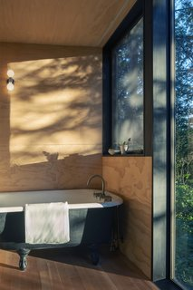 In the master bathroom is a reclaimed, cast iron tub that creates the feeling of soaking in the outdoors without interrupting moments of repose.