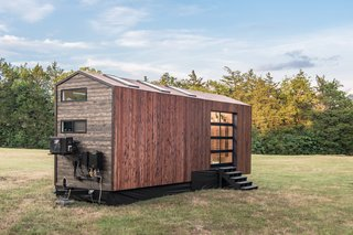 They tiny house connects to the outdoors with clerestory windows, floor-to-ceiling windows, skylights, and a garage door that opens up an entire wall.