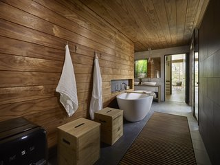 Wooden surfaces give the bathroom and sauna a warm, spa-like feel. A fully glazed wall connects the sauna to the great outdoors.