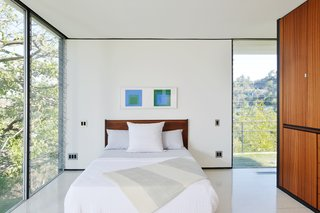 Fully glazed walls open the bedroom to the green outdoors.
