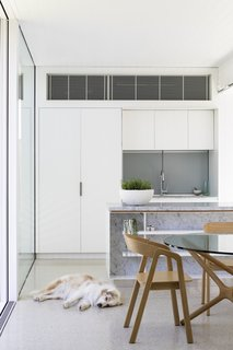 An open-plan kitchen and dining area within the addition feature white cabinets.