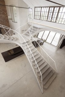 The staircase branches out to hug both sides of the loft's upper walls.