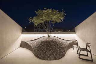 A Zen rock garden on one of the balconies with a Vitra Tip Ton chair.