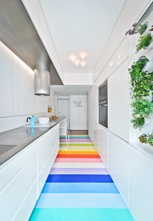 In the kitchen, a mini vertical garden provides fresh aromatic herbs thanks to a mix of direct sun and specialized artificial lighting. A vibrant rubber floor leads the eye forward.
