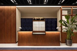 The reception features terrazzo flooring and teak and walnut casework.