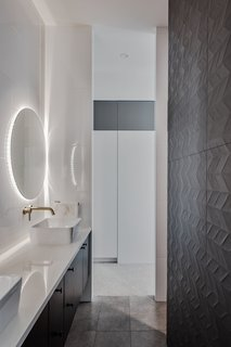 Dark, full-height tiles create a dramatic backdrop in the twin shower room.