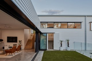 Flush-set plasterboard walls and ceilings reflect the clean, white weatherboard cladding used externally.