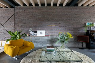 The living room features an exposed brick wall and ceiling beams.