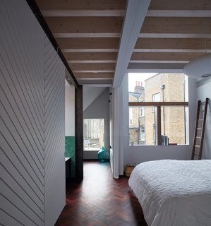 Large windows bring sunlight into the bedroom.
