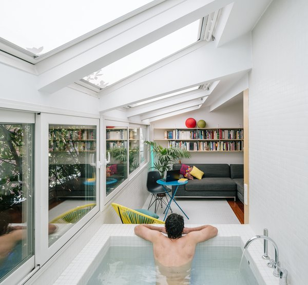 A sunken bathtub is positioned right next to a giant window, just off the living lounge.