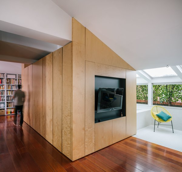 The pine volume creates a corridor that leads from the living area to the bedroom.