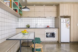 A white tile backsplash sets the kitchen and dining apart from the concrete and wood walls in the rest of the home.