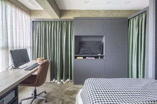 Green curtains in the gray cabinet and partition provide privacy for the bedroom and work space.