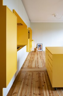 """A bright, yellow """"function wall"""" saves space and visually expands this compact apartment."""