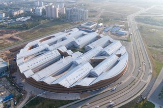 The first building that's part of a new tech campus being developed, the Skolkovo Institute of Science and Technology University's East Wing Building is designed in the form of a massive, partially filled ring with a 919-foot diameter, and jigsaw-like roofline.