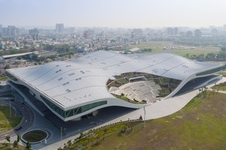 Inspired by the undulating canopy of the region's banyan trees, the five venues of this performing arts center are located underneath a single, sweeping roof and connected to its parkland site. The National Kaohsiung Center for the Arts rests on a site that formerly hosted a military training base, and represents the city's changing identity.