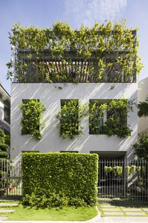 The permeable top floor allows greenery in to the home to spill out toward the neighborhood.
