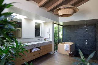 The luxurious step-down ensuite bathroom has a shower, Japanese-style soaking tub, and extensive closet space, plus a vanity.