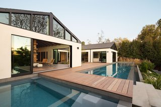A bridge traverses the pool, connecting to a lower lounge deck and grassy yard. The home includes a guesthouse with a flexible space for a studio, gallery, gym, or home office.