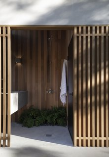 An outdoor poolside shower and toilet.