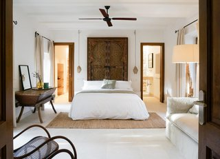 Two doors in this bedroom aren't symmetrically located, but by using matching wood frames, a centered bed with centered light fixtures, and matching window treatments, the discrepancy in the doors is rendered almost indecipherable.
