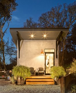 An orange lantern lights the way to an angular gray structure.