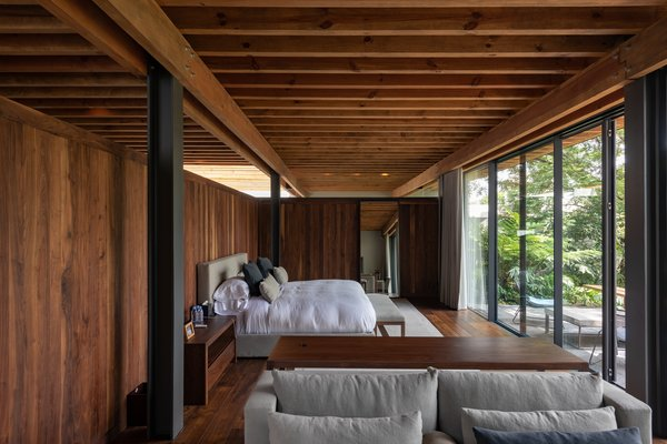 The intimacy of Casa Santísimo is exemplified in the bedroom—JJRR Arquitectura installed warm wood walls to contrast with the serene forest views.