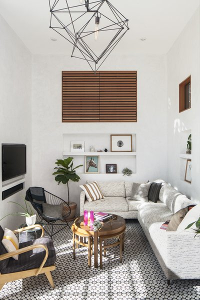 The sunny double height living space features custom concrete tiles,  plaster walls with built-in niche storage, and a custom slatted wood door leads to an indoor storage area.