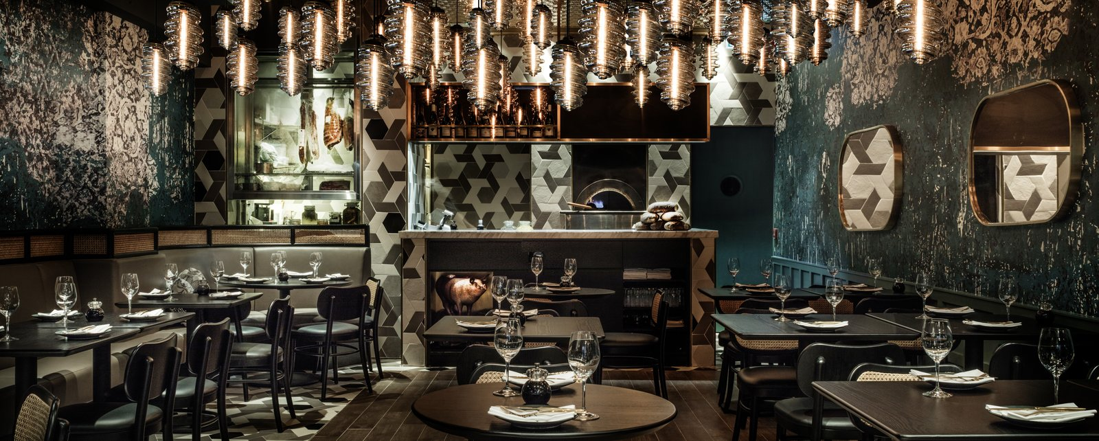 """The entire space is pulled into a central focus by the """"hearth"""", a wood fired oven. Set within the open kitchen, it enables the chef to survey his empire and directly interact with his diners. The space is after all a theatre for the chef and his diners.    Photo 1 of 1 in Emma Maxwell designs  12,000 Francs."""