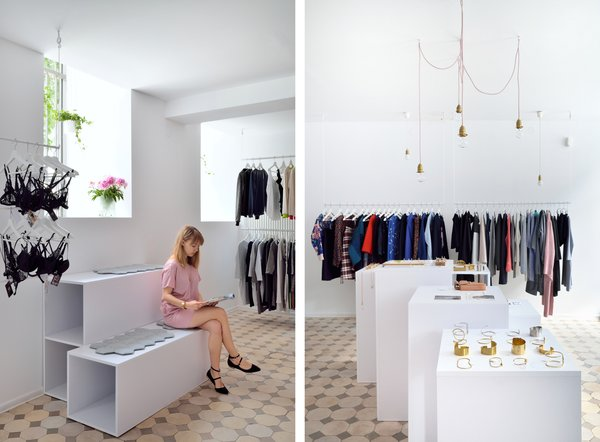 Clothes racks hang from the ceiling to add lightness and make the space feel bigger.