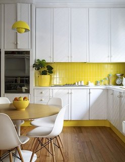 This sunny yellow kitchen successfully mixes vintage charm with mid-century furniture.