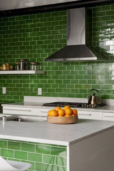 Stem green subway tiles, crisp against white marble countertops, unite this kitchen's island and galley counter.