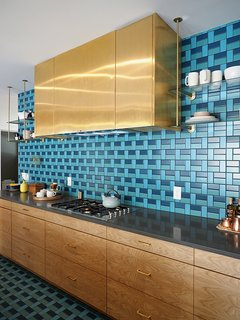 This kitchen, from the 2015 Sunset Idea House, features a pattern of blue & turquoise tiles from the back wall all the way to the kitchen floor.