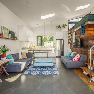 8 Modern In-Law Units - Photo 8 of 16 - The interior of the space is filled with natural light, thanks to the vaulted ceiling and skylights. The owner's workspace resides in an upper loft—a volume highlighted by salvaged wood panels.
